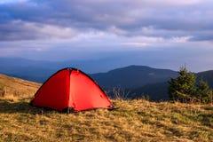 Rött tält under moln i berg Arkivbild