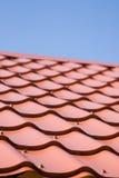 Rött tak av metall som taklägger på himlen arkivfoto