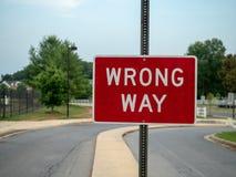 Rött tecken för fel väg på en lokal grannskapkörbana med utrymme till det vänstert royaltyfri fotografi