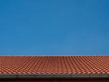 Rött tegelplattatak på bakgrund för blå himmel arkivfoton