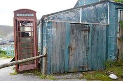 Rött telefonbås bredvid ett gammalt garage Arkivbilder