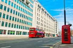 Rött telefonbås för brittiska symboler och röd buss i London Royaltyfri Bild