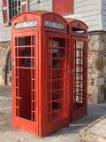 Rött telefonbås i Antigua för kreditkortar endast arkivbilder