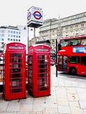 Rött telefonbås och röd buss Royaltyfri Fotografi