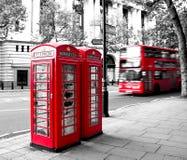 Rött telefonbås och röd buss Royaltyfri Bild