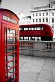 Rött telefonbås och röd buss Royaltyfri Foto