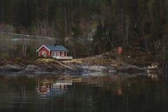 Rött trähus nära sjön mot bakgrunden av skogen och bergen Reflexionen bevattnar in royaltyfri bild