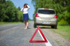 Rött triangeltecken och bruten bil på vägrenen Arkivbilder