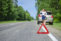 Rött triangeltecken på vägen och den unga kvinnan som kallar för bil som Royaltyfri Bild