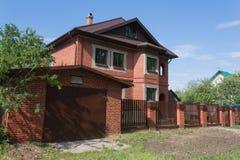 Rött två-våning tegelstenhus med garaget bak det höga staketet royaltyfria bilder