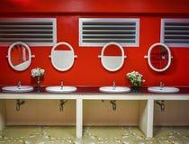 Rött väggbadrum med spegeln och vasken Arkivfoto