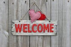 Rött välkommet tecken som hänger på den wood dörren med ginghamhjärta Royaltyfri Bild