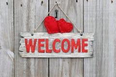 Rött välkommet tecken som hänger på den wood dörren med röda hjärtor och järntangenter Royaltyfria Foton