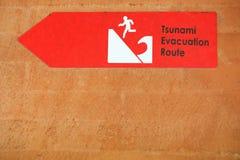 Rött varningstecken för tsunami på väggen faratecken arkivbilder