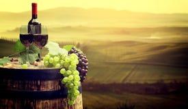 Rött vin buteljerar, och wineexponeringsglas wodden på trumman Härliga Tusca Arkivbild