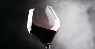 Rött vin färgstänk i ett exponeringsglas, torra cabernet - sauvignon, mörk backgr arkivbild