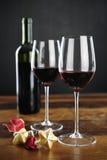 Rött vin, flaska och julstjärnor Arkivfoto