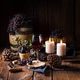 Rött vin från en trumma med druvor och ett exponeringsglas av vin royaltyfria foton