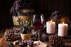 Rött vin från en trumma med druvor och ett exponeringsglas av vin arkivbild