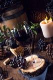 Rött vin från en trumma med druvor och ett exponeringsglas av vin arkivfoton