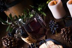 Rött vin från en trumma med druvor och ett exponeringsglas av vin fotografering för bildbyråer