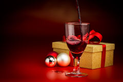 Rött vin hällde in i Glass framme av guld- gåva Arkivbild