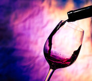 Rött vin hällde in i vinglaset royaltyfria foton