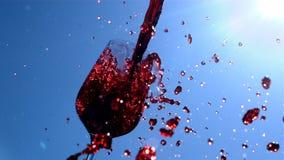 Rött vin häller in till ett exponeringsglas med blå himmel och solsken på bakgrund i ultrarapid stock video