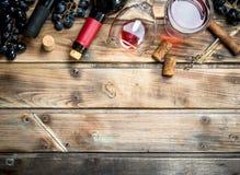 Rött vin i ett exponeringsglas med druvor och en korkskruv fotografering för bildbyråer