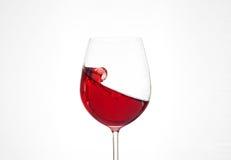 Rött vin i ett exponeringsglas på en vit bakgrund Begreppet av beveraen Fotografering för Bildbyråer