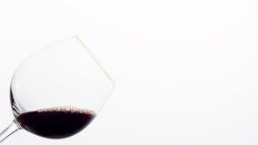 Rött vin i ett exponeringsglas som vippas på till en sida Royaltyfri Bild