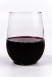 Rött vin i ett stemless vinexponeringsglas arkivfoto