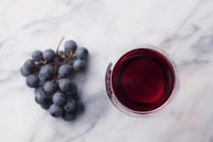 Rött vin i exponeringsglas med den nya druvan på marmortabellbakgrund Top beskådar royaltyfria bilder