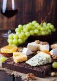 Rött vin i exponeringsglas med ost, honung, muttrar och druvan royaltyfria foton