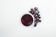 Rött vin i gräs och mogna druvor som isoleras på vit royaltyfri foto