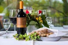 Rött vin med flaskan och exponeringsglas på en tabell Fotografering för Bildbyråer