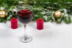 Rött vin med julobjekt som täckas med ny snö Arkivfoto