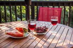 Rött vin med körsbär och vattenmelon på en yttersidatabell Arkivbild