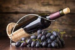 Rött vin med klungan av mörker - blåa druvor på trätabellen Arkivfoton
