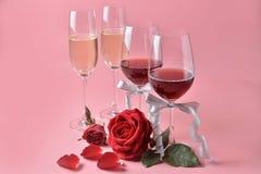 Rött vin och champagne i exponeringsglas, med rosen som är längst ner på rosa bakgrund Begrepp av dagen för valentin` s royaltyfri bild