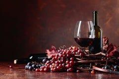 Rött vin och nya druvor med torkat upp vinrankasidor arkivfoton