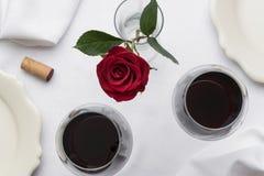 Rött vin på den vita linnetabellinställningen Royaltyfri Bild