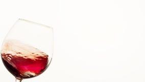 Rött vin som är rörande upp i ett exponeringsglas Arkivfoto