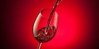 Rött vin som häller in i ett exponeringsglas på röd bakgrund Royaltyfri Bild