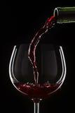 Rött vin som häller in i ett vinexponeringsglas Arkivbilder