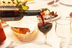 Rött vin som häller in i ett vinexponeringsglas, det anseende på tabellen Royaltyfri Fotografi