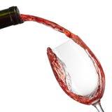 Rött vin som häller in i exponeringsglas med färgstänk som isoleras på vit arkivfoto