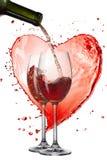Rött vin som häller in i exponeringsglas mot hjärta av färgstänk Royaltyfria Foton