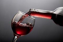Rött vin som häller in i exponeringsglas på svart Royaltyfri Foto