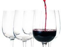 Rött vin som häller in i tomt exponeringsglas Fotografering för Bildbyråer